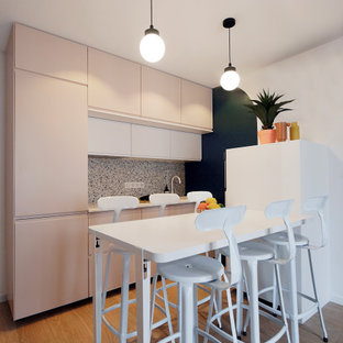 Photo of a small modern single-wall open plan kitchen in Paris with a single-bowl sink, beaded inset cabinets, pink cabinets, laminate benchtops, multi-coloured splashback, ceramic splashback, white appliances, vinyl floors, beige floor and white benchtop.