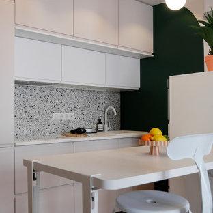 Idéer för ett litet modernt vit linjärt kök med öppen planlösning, med en enkel diskho, luckor med profilerade fronter, laminatbänkskiva, flerfärgad stänkskydd, stänkskydd i keramik, vita vitvaror, vinylgolv och beiget golv