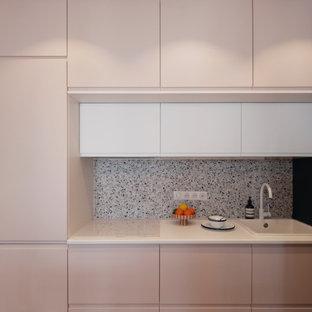 Cette photo montre une petit cuisine ouverte linéaire moderne avec un évier 1 bac, un placard à porte affleurante, des portes de placard rose, un plan de travail en stratifié, une crédence multicolore, une crédence en carreau de céramique, un électroménager blanc, un sol en vinyl, un sol beige et un plan de travail blanc.