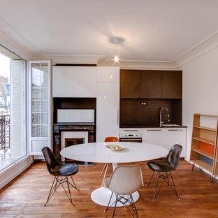 Idée de décoration pour une petite cuisine américaine linéaire design avec un placard à porte plane, des portes de placard blanches, une crédence blanche, un sol en bois foncé et aucun îlot.