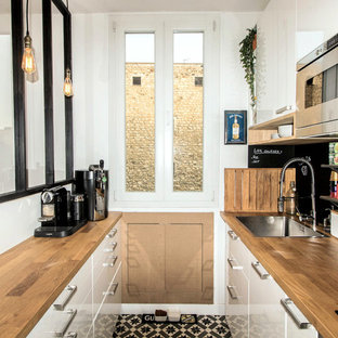 Inspiration for a small industrial galley open plan kitchen in Paris with an undermount sink, flat-panel cabinets, white cabinets, wood benchtops, black splashback, slate splashback, panelled appliances, cement tiles and no island.