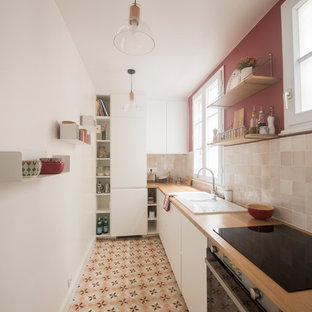 This is an example of a mid-sized midcentury l-shaped separate kitchen in Paris with a double-bowl sink, white cabinets, wood benchtops, beige splashback, terra-cotta splashback, panelled appliances, cement tiles, no island, multi-coloured floor and brown benchtop.