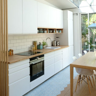 Mid-sized scandinavian single-wall open plan kitchen in Paris with an undermount sink, flat-panel cabinets, white cabinets, wood benchtops, white splashback, ceramic splashback, panelled appliances, cement tiles, no island and blue floor.