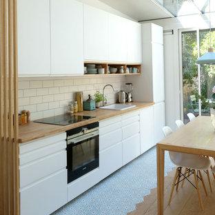 На фото: прямая кухня-гостиная среднего размера в скандинавском стиле с врезной раковиной, плоскими фасадами, белыми фасадами, деревянной столешницей, белым фартуком, фартуком из керамической плитки, техникой под мебельный фасад, полом из цементной плитки и синим полом без острова с