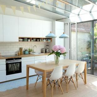 パリの中サイズの北欧スタイルのおしゃれなキッチン (フラットパネル扉のキャビネット、白いキャビネット、木材カウンター、白いキッチンパネル、セラミックタイルのキッチンパネル、パネルと同色の調理設備、セメントタイルの床、アイランドなし、ドロップインシンク、青い床) の写真