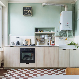 Photo of a small scandinavian single-wall open plan kitchen in Nantes with a farmhouse sink, beaded inset cabinets, black appliances, ceramic floors, white benchtop, light wood cabinets, solid surface benchtops, ceramic splashback, no island and red floor.