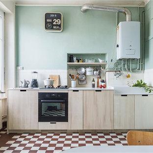 ナントの小さい北欧スタイルのおしゃれなキッチン (エプロンフロントシンク、インセット扉のキャビネット、黒い調理設備、セラミックタイルの床、白いキッチンカウンター、淡色木目調キャビネット、人工大理石カウンター、セラミックタイルのキッチンパネル、アイランドなし、赤い床) の写真