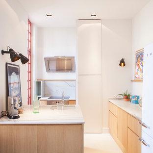 Idée de décoration pour une petite cuisine design en L avec un plan de travail en granite, béton au sol, un évier encastré, un placard à porte plane, des portes de placard en bois clair, une crédence blanche, une crédence en dalle de pierre, un électroménager blanc, une péninsule, un sol beige et un plan de travail blanc.
