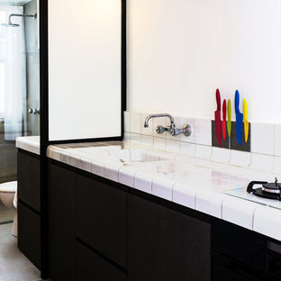Inspiration for a small contemporary single-wall eat-in kitchen in Paris with beaded inset cabinets, with island, an integrated sink, tile benchtops, white splashback, porcelain splashback, black appliances and ceramic floors.