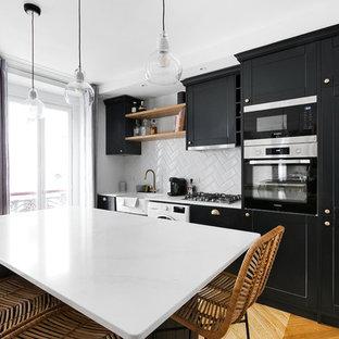 Aménagement d'une cuisine contemporaine avec un évier de ferme, un placard à porte shaker, des portes de placard noires, une crédence blanche, une crédence en carreau de céramique, un électroménager noir, un sol en bois brun, un îlot central, un sol beige et un plan de travail blanc.