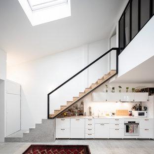 Aménagement d'une grand cuisine linéaire contemporaine avec un évier posé, un placard à porte plane, des portes de placard blanches, un électroménager blanc, aucun îlot, un sol gris et un plan de travail blanc.