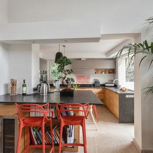 Réalisation d'une grand cuisine design en U avec un évier encastré, un placard à porte plane, des portes de placard en bois brun, une crédence blanche, une crédence en fenêtre, un électroménager en acier inoxydable, un sol beige et un plan de travail noir.