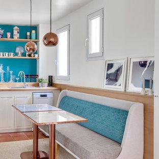 パリの中サイズのエクレクティックスタイルのおしゃれなキッチン (淡色木目調キャビネット、木材カウンター、カラー調理設備、テラコッタタイルの床、茶色い床) の写真