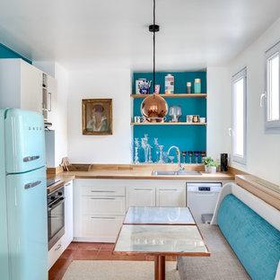 Cette photo montre une cuisine américaine éclectique en L de taille moyenne avec un plan de travail en bois, un électroménager de couleur, un sol en carreau de terre cuite, un sol marron, un évier posé, des portes de placard blanches et une crédence bleue.