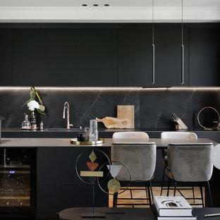 Cette photo montre une cuisine ouverte tendance avec un placard à porte plane, des portes de placard noires, une crédence noire, une crédence en dalle de pierre, un sol en bois clair, un îlot central et un plan de travail gris.