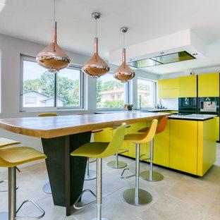 Réalisation d'une cuisine design avec un placard à porte plane, des portes de placard jaunes, 2 îlots et un sol beige.