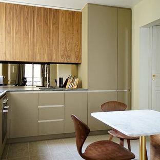 Inspiration pour une petite cuisine américaine design en L avec un évier encastré, un placard à porte plane, des portes de placard beiges, aucun îlot, un sol gris et un plan de travail gris.