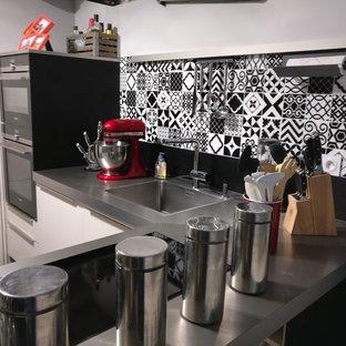 ディジョンの小さいコンテンポラリースタイルのおしゃれなキッチン (アンダーカウンターシンク、インセット扉のキャビネット、白いキャビネット、ステンレスカウンター、黒いキッチンパネル、セメントタイルのキッチンパネル、シルバーの調理設備、ラミネートの床、黒い床) の写真