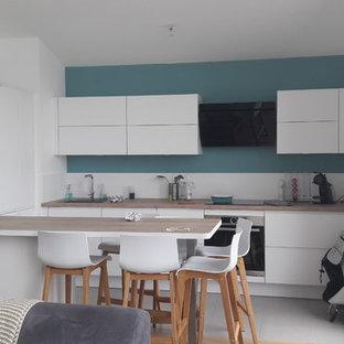 Esempio di una cucina scandinava di medie dimensioni con lavello a vasca singola, ante a filo, top in legno, paraspruzzi in legno, elettrodomestici in acciaio inossidabile, pavimento in cementine, isola, pavimento grigio, ante bianche e paraspruzzi bianco