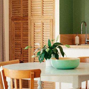 Idées déco pour une cuisine ouverte romantique en L de taille moyenne avec un évier encastré, un placard à porte persienne, des portes de placard en bois clair, un plan de travail en bois, une crédence en bois, un sol en bois clair, une crédence marron et un sol beige.