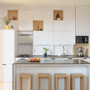 Aménagement d'une cuisine parallèle contemporaine de taille moyenne avec un évier posé, un placard à porte plane, des portes de placard blanches, un électroménager encastrable, un sol en bois clair, un îlot central, un sol beige et un plan de travail gris.