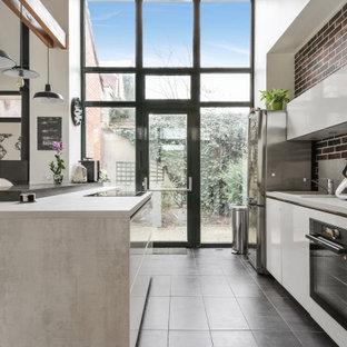 パリの広いコンテンポラリースタイルのおしゃれなキッチン (フラットパネル扉のキャビネット、白いキャビネット、グレーの床、グレーのキッチンカウンター、アンダーカウンターシンク、ラミネートカウンター、グレーのキッチンパネル、木材のキッチンパネル、パネルと同色の調理設備、セラミックタイルの床、表し梁) の写真