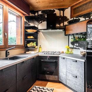 Réalisation d'une petit cuisine design avec des portes de placard noires, un plan de travail en stratifié, un évier posé, un placard à porte plane, une crédence grise, un électroménager noir, un sol en bois brun et un sol orange.