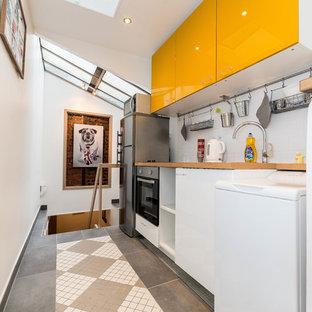 Idée de décoration pour une petite cuisine ouverte linéaire design avec un placard à porte plane, des portes de placard jaunes, un plan de travail en bois, une crédence blanche et aucun îlot.