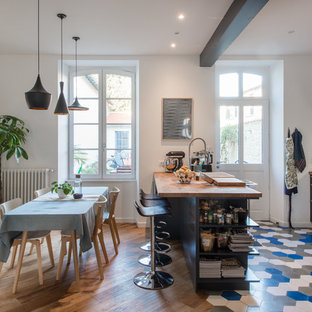 Scandinavian l-shaped eat-in kitchen in Montpellier with raised-panel cabinets, blue cabinets, wood benchtops, white splashback, subway tile splashback, stainless steel appliances, a peninsula, multi-coloured floor and brown benchtop.