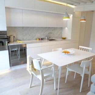 Aménagement d'une cuisine ouverte linéaire contemporaine de taille moyenne avec un placard à porte plane, des portes de placard blanches, une crédence blanche, une crédence en dalle de pierre, un sol en bois clair et aucun îlot.