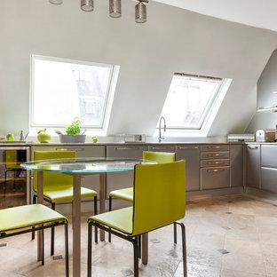 Idées déco pour une grand cuisine américaine contemporaine en L avec un placard à porte plane, des portes de placard grises et un plan de travail en inox.