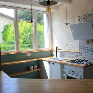 Design ideas for a small midcentury u-shaped eat-in kitchen in Bordeaux with an undermount sink, beaded inset cabinets, white cabinets, wood benchtops, multi-coloured splashback, cement tile splashback, white appliances, cement tiles, with island and beige floor.