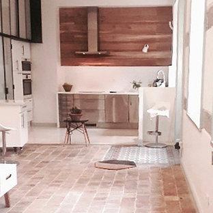 На фото: п-образная кухня-гостиная среднего размера в стиле модернизм с двойной раковиной, стеклянными фасадами, кухней из нержавеющей стали, столешницей из ламината, белым фартуком, фартуком из керамической плитки, техникой из нержавеющей стали, полом из терракотовой плитки, островом, розовым полом и белой столешницей с