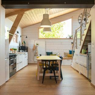 Idée de décoration pour une très grand cuisine nordique avec un évier de ferme, un placard à porte shaker, des portes de placard blanches, un plan de travail en bois, un électroménager noir, un sol en bois clair, un sol beige et un plan de travail beige.