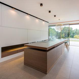 Esempio di una cucina minimalista con ante lisce, ante in legno scuro, elettrodomestici da incasso, isola e pavimento beige