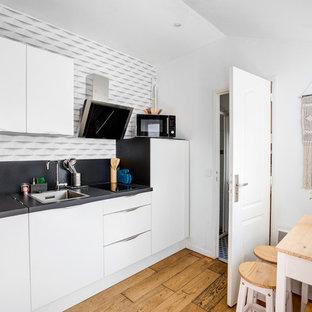 Inspiration pour une petit cuisine américaine linéaire nordique avec des portes de placard blanches, un plan de travail en stratifié, une crédence noire, aucun îlot, un plan de travail noir, un évier posé, un placard à porte plane, un sol en bois brun et un sol marron.