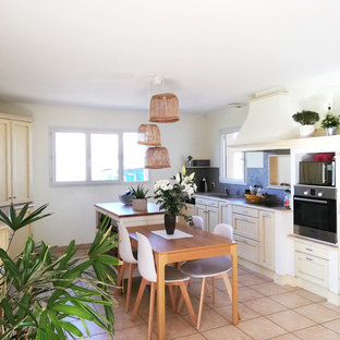 Photo of a large beach style galley open plan kitchen in Nantes with an undermount sink, recessed-panel cabinets, beige cabinets, granite benchtops, grey splashback, ceramic floors, with island, pink floor and pink benchtop.