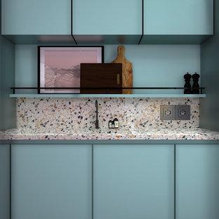 Diseño de cocina lineal, retro, de tamaño medio, abierta, con fregadero integrado, armarios con rebordes decorativos, puertas de armario azules, encimera de terrazo, salpicadero multicolor, electrodomésticos con paneles, suelo de cemento, suelo gris y encimeras multicolor