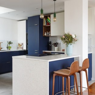 Inspiration for a large contemporary u-shaped open plan kitchen in London with a submerged sink, flat-panel cabinets, blue cabinets, granite worktops, white splashback, porcelain splashback, integrated appliances, ceramic flooring, a breakfast bar, grey floors and white worktops.