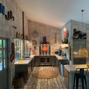 Exemple d'une grand cuisine ouverte montagne en U avec un évier posé, un placard à porte plane, une façade en inox, une crédence grise, une crédence en dalle métallique, un électroménager en acier inoxydable, un sol en bois brun, un îlot central, un sol gris et un plan de travail gris.