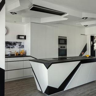 Inspiration pour une grand cuisine ouverte design en L avec un placard à porte plane, un îlot central, un évier 2 bacs, une crédence blanche, un électroménager en acier inoxydable, un sol en bois peint, un sol gris et un plan de travail noir.