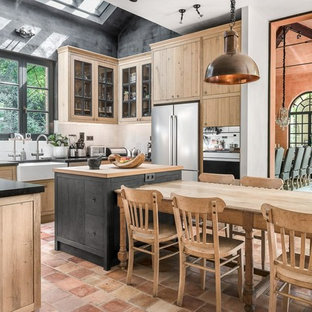 Inspiration for a farmhouse u-shaped kitchen/diner in Marseille with a belfast sink, glass-front cabinets, light wood cabinets, white splashback, stainless steel appliances, terracotta flooring, an island and orange floors.