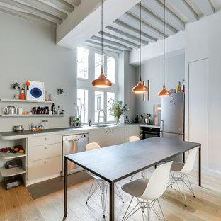 Réalisation d'une cuisine américaine nordique en L de taille moyenne avec un placard à porte plane, des portes de placard blanches, un électroménager en acier inoxydable et un sol en bois clair.