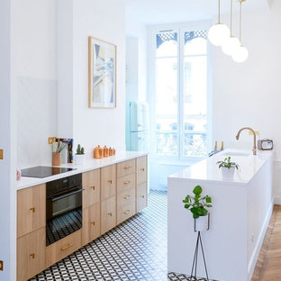 Design ideas for a mid-sized contemporary galley open plan kitchen in Lyon with an integrated sink, light wood cabinets, white splashback, black appliances, cement tiles, with island and multi-coloured floor.