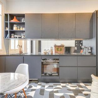 Idée de décoration pour une cuisine ouverte linéaire nordique avec un évier 1 bac, un placard à porte plane, des portes de placard grises, un plan de travail en inox, une crédence en carreau de miroir, aucun îlot et un sol multicolore.