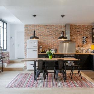 Inspiration pour une grand cuisine américaine urbaine en L avec un évier posé, des portes de placard noires, une crédence métallisée, une crédence en dalle métallique, un électroménager en acier inoxydable, un sol en bois clair et aucun îlot.
