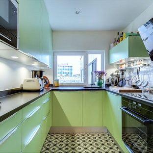This is an example of a mid-sized contemporary u-shaped separate kitchen in Paris with flat-panel cabinets, green cabinets, granite benchtops, white splashback, subway tile splashback, black appliances, ceramic floors and no island.
