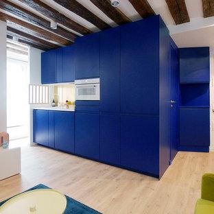 Idee per una cucina moderna di medie dimensioni con lavello a vasca singola, ante a filo, ante blu, top in laminato, paraspruzzi a effetto metallico, elettrodomestici da incasso, parquet chiaro, pavimento beige, top bianco e travi a vista