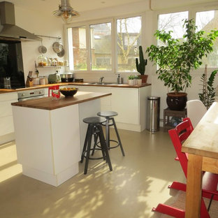 Design ideas for a mid-sized midcentury l-shaped open plan kitchen in Rennes with an undermount sink, flat-panel cabinets, white cabinets, wood benchtops, white splashback, window splashback, stainless steel appliances, concrete floors, with island, beige floor and brown benchtop.