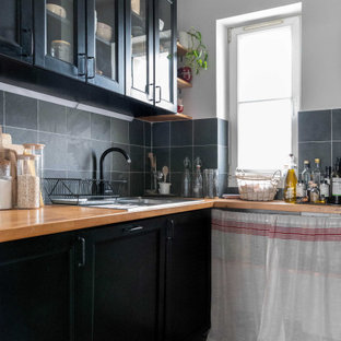This is an example of a small midcentury u-shaped separate kitchen in Paris with an undermount sink, black cabinets, wood benchtops, grey splashback, slate splashback, black appliances, cement tiles and grey floor.